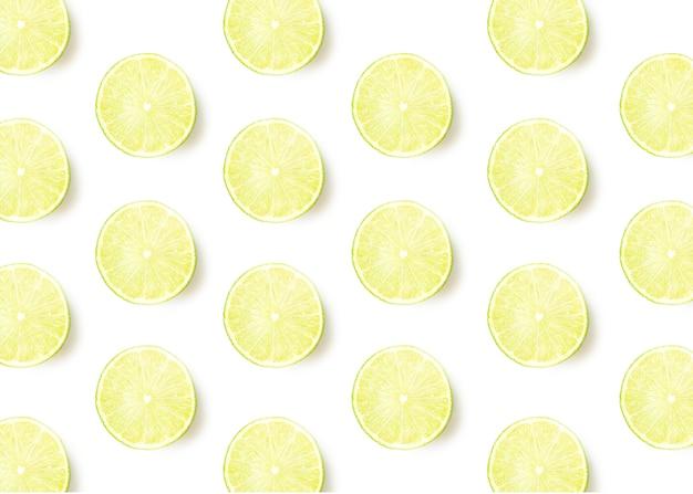 Tranches de citron vert avec ombre sur fond blanc