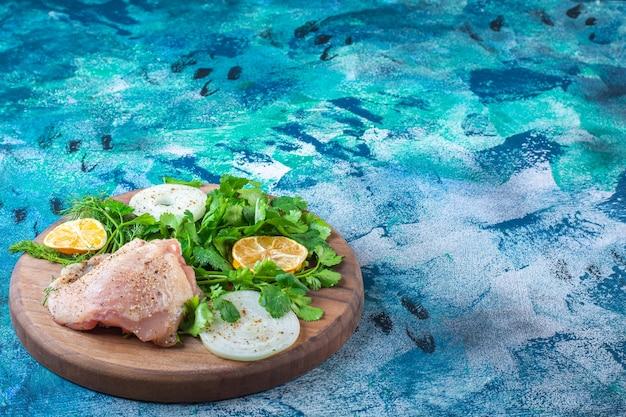 Tranches de citrons, d'oignons et de persil avec de la viande de poulet sur une planche
