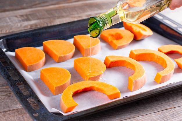 Tranches de citrouille brillantes préparées pour la cuisson au four avec de l'huile d'olive, ingrédient alimentaire