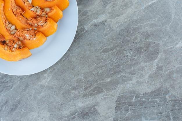 Tranches de citrouille disposées en rang, sur la table en marbre.