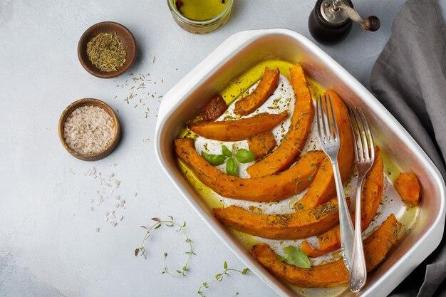 Tranches de citrouille frites aux herbes et poivrons, huile d'olive sur béton gris ou pierre.