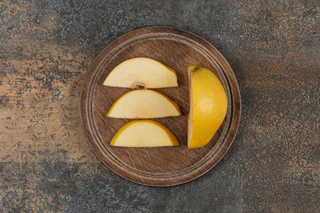 Tranches de coing jaune sur planche de bois