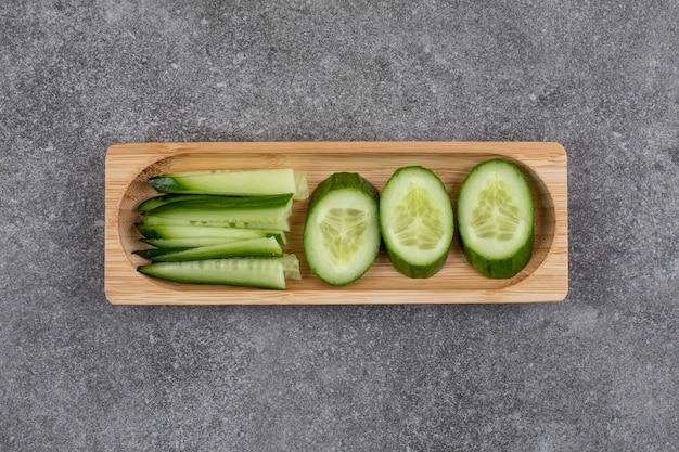 Tranches de concombre bio sur planche de bois