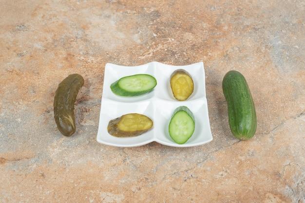 Tranches de concombre mariné et frais sur plaque blanche