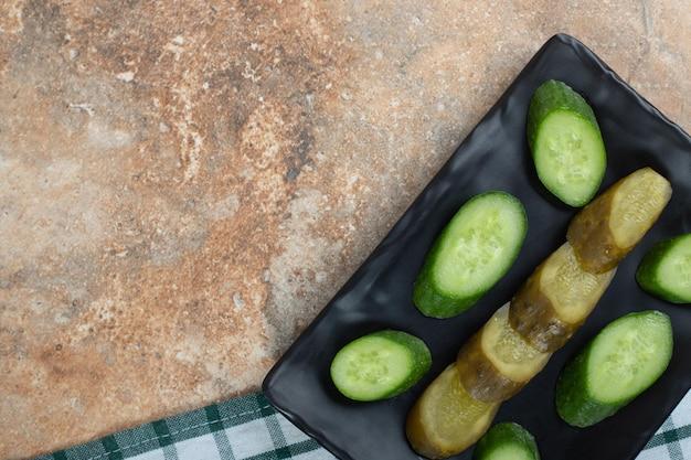 Tranches de concombre mariné et frais sur plaque noire