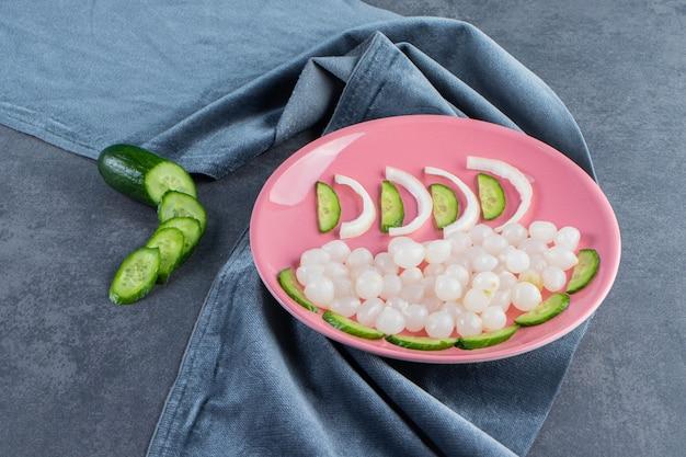 Tranches de concombre et de petits oignons marinés sur une assiette sur les morceaux de tissu, sur la surface en marbre.