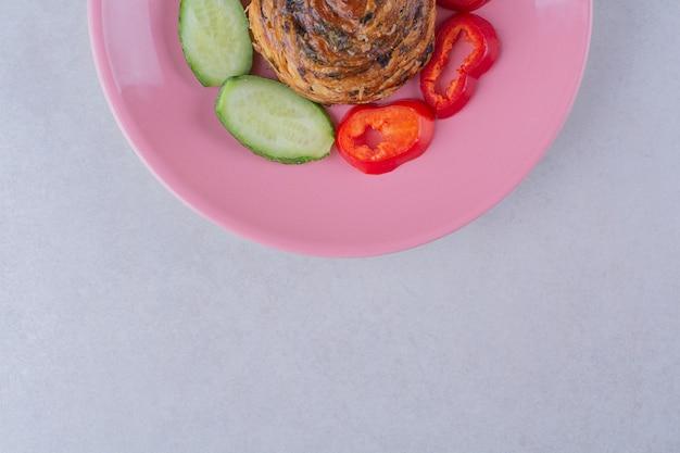 Tranches de concombre et de poivron autour du cookie sur une assiette sur une table en marbre.