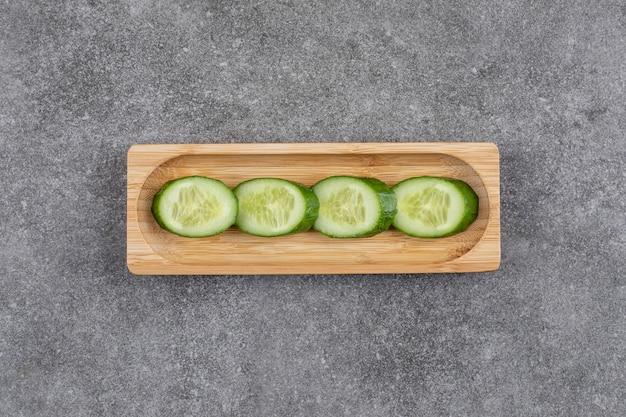 Tranches de concombre sain bio frais sur planche de bois