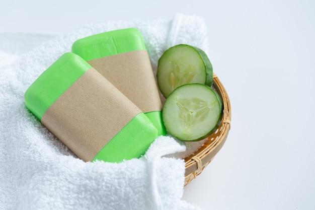 Tranches de concombre et savon sur fond blanc