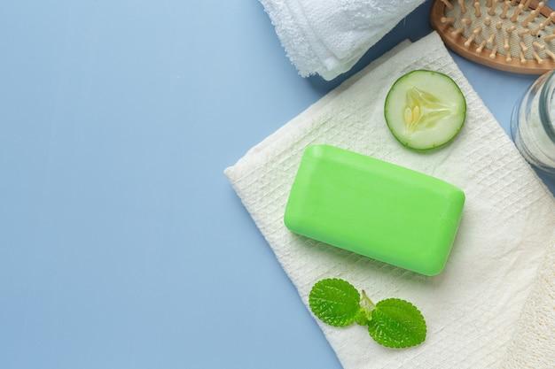 Tranches de concombre et savon sur fond bleu clair