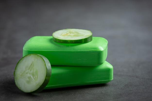 Tranches de concombre et savon sur fond sombre