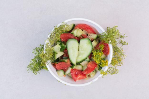 Tranches de concombres et de tomates dans un bol blanc avec des verts