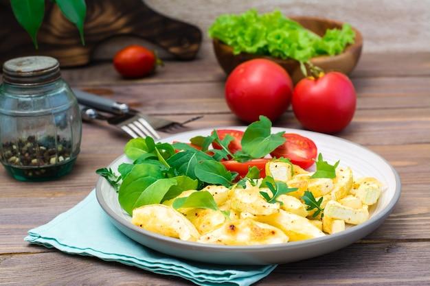 Tranches de courgettes appétissantes cuites au four avec du fromage sur une assiette avec des tomates et de la roquette sur une table en bois