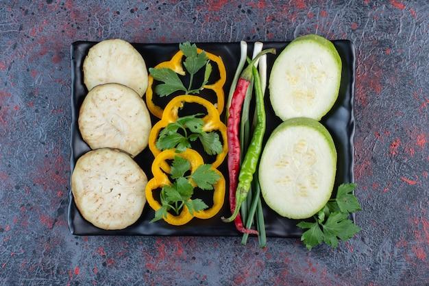 Tranches de courgettes, d'aubergines et de poivrons avec piments forts et oignons nouveaux sur un plateau sur fond de couleur sombre. photo de haute qualité