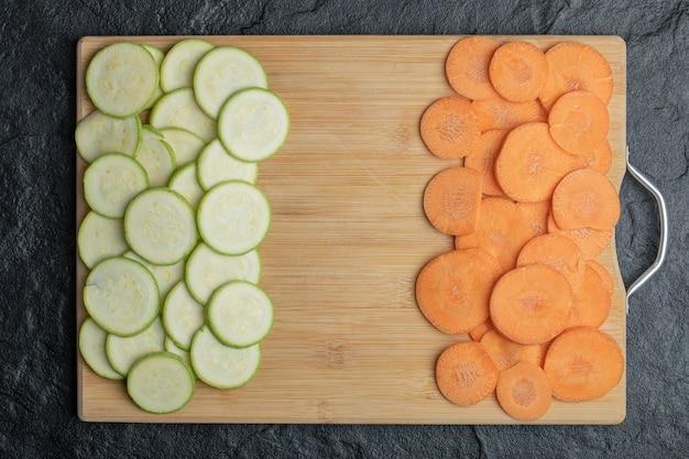 Tranches de courgettes et carottes séparées sur planche de bois. photo de haute qualité