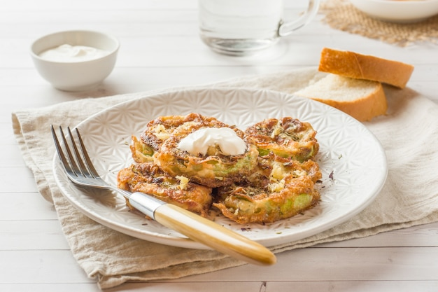 Tranches de courgettes frites dans une pâte à l'oeuf avec de l'ail sur une assiette.