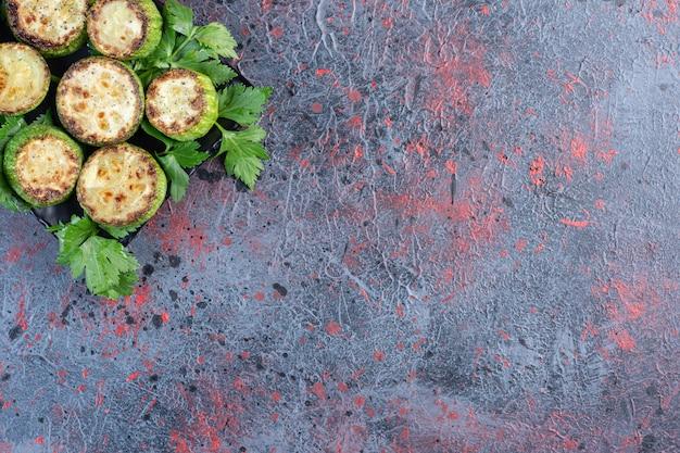 Tranches de courgettes frites sur un plateau orné de persil sur table noire.