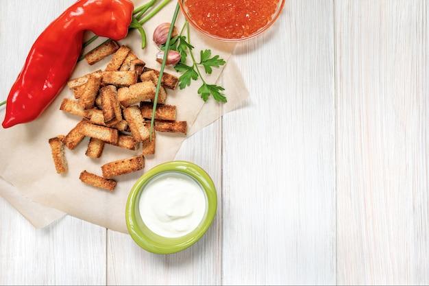 Tranches de croûtons frits avec sauce à la crème sure, poivron rouge, caviar et gousses d'ail sur une planche de bois blanc