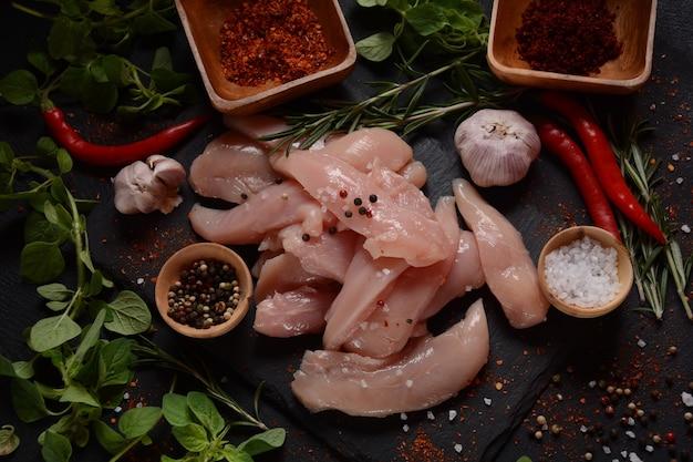Tranches crues non cuites de poitrine de poulet désossée pour barbecue viande avec ingrédients pour la cuisson