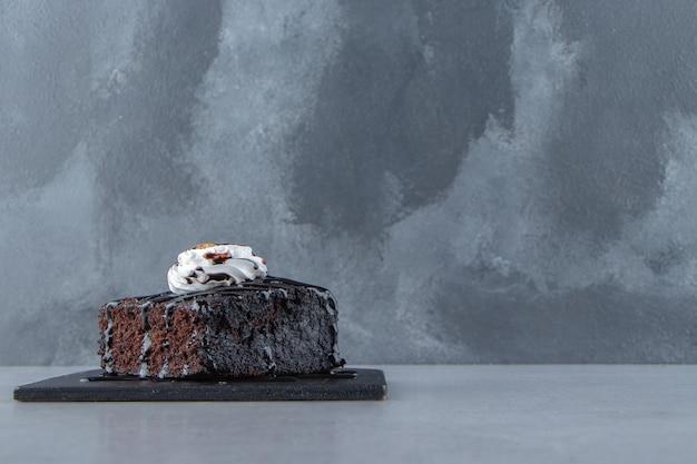 Tranches de délicieux brownie au chocolat avec de la crème sur une planche à découper. photo de haute qualité