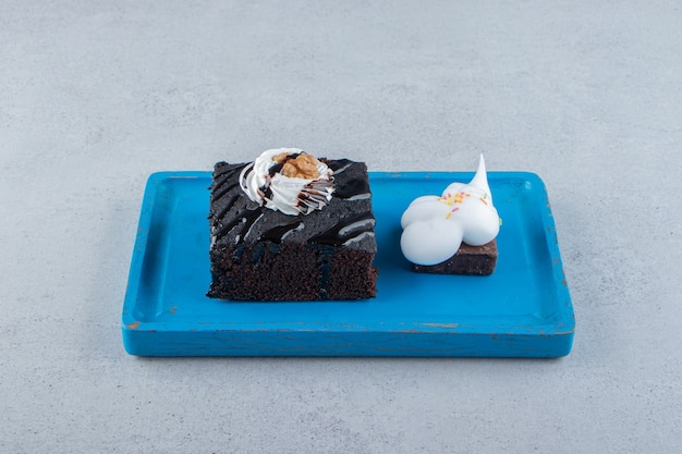 Tranches de délicieux brownie au chocolat avec de la crème sur une plaque bleue. photo de haute qualité
