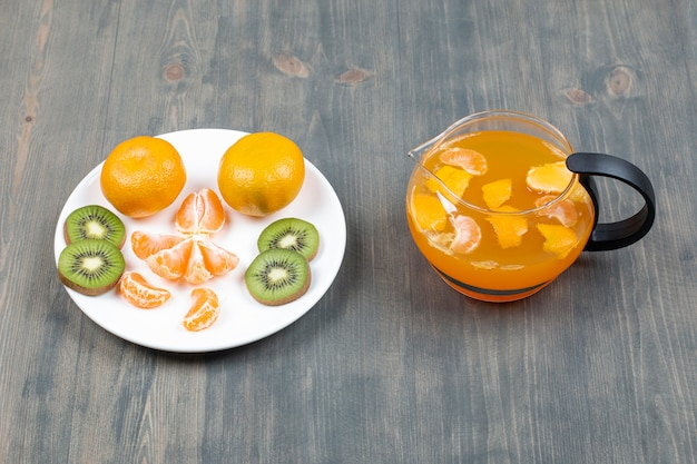 Tranches de divers fruits avec un bocal en verre de jus