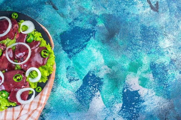 Tranches de divers légumes et foies de poulet sur la planche à découper sur le torchon