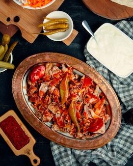 Tranches de doner de poulet garnies de sauce épicée servies avec poivrons et tomates