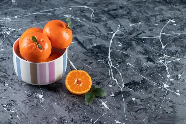 Tranches et entières de fruits orange frais avec des feuilles placées sur un bol coloré.