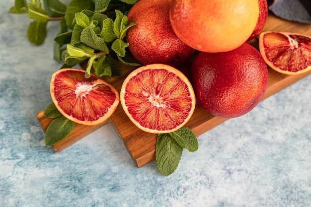 Tranches et entières d'oranges sanguines siciliennes juteuses et mûres sur une planche à découper en bois avec menthe, surface en béton bleu