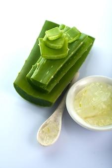 Des tranches de feuilles d'aloe vera et du gel d'aloe vera dans un bol. l'aloe vera est une phytothérapie très utile pour les soins de la peau et des cheveux.