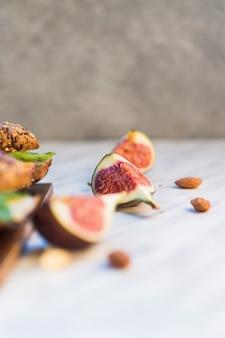 Tranches de figue fraîche et amandes près de hot-dog sur une planche en bois sur fond blanc