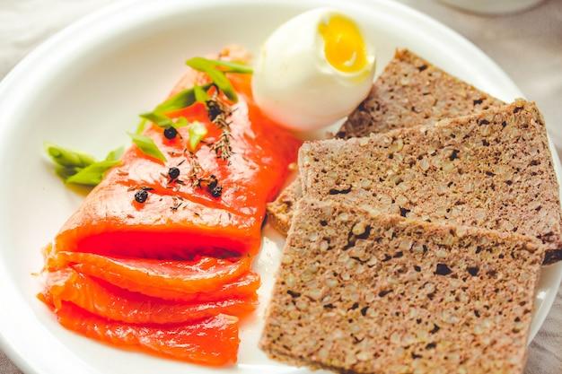 Tranches de filet de poisson cru salé avec oeuf et morceau de pain de sarrasin sans gluten. repas régime paléo. concept sain de produits riches en protéines et faibles en glucides.