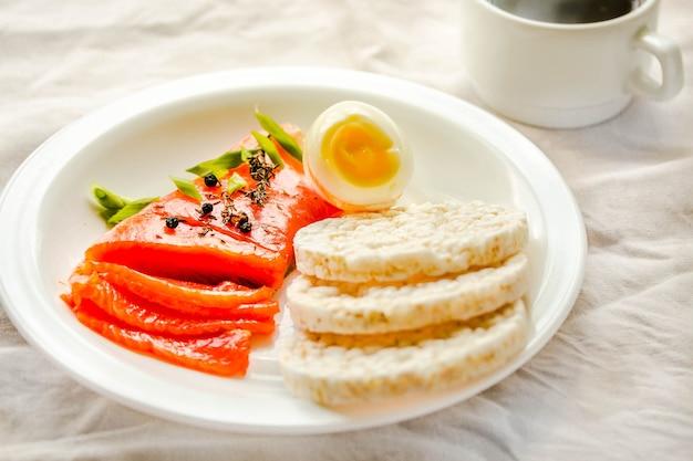 Tranches de filet de poisson cru salé avec œufs et galettes de riz. sélection de bonnes sources de matières grasses - concept d'alimentation saine. concept de régime cétogène. mise au point sélective