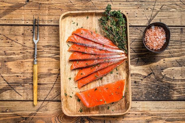 Tranches de filet de saumon salé dans un plateau en bois avec du thym
