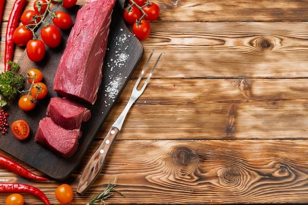 Tranches de filet de viande crue sur planche de bois
