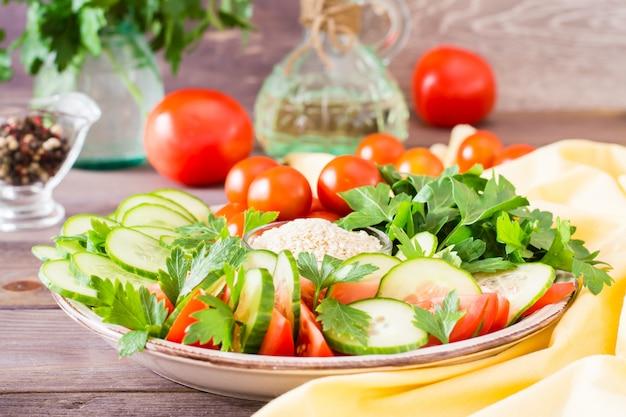 Tranches fraîches de concombres, tomates et feuilles de persil sur une plaque sur une table en bois