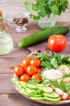 Tranches fraîches de concombres, tomates, graines de sésame dans un bol et feuilles de persil sur une plaque sur une table en bois.