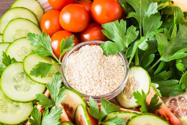 Tranches fraîches de concombres, tomates, graines de sésame dans un bol et feuilles de persil sur une plaque