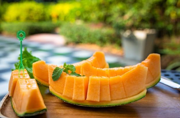 Tranches fraîches de melon sucré orange mis sur une plaque en bois.