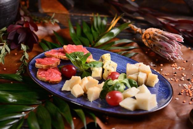 Tranches de fromage aux raisins dans une assiette bleue. avec décor floral