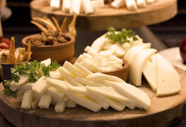 Tranches de fromage blanc avec des légumes verts sur une planche de bois. focale sélective