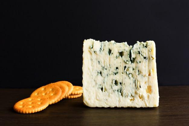 Tranches de fromage bleu danois et des biscuits sur une vieille table en bois.