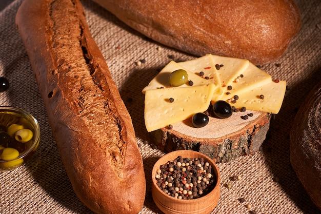 Tranches de fromage sur un bureau en bois entre différents pains