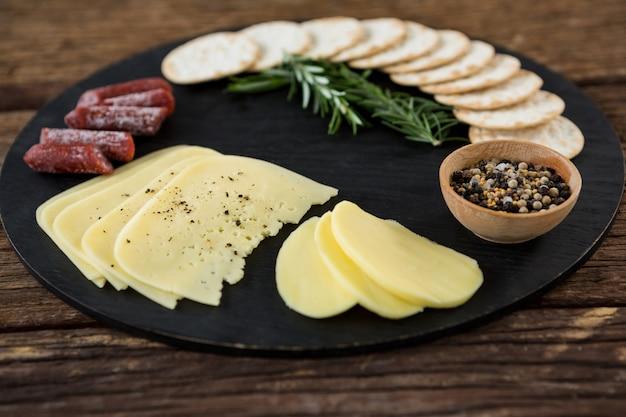 Tranches de fromage, chips de nacho et herbes de romarin sur plaque