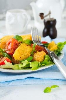 Tranches de fromage frit dans du gruau de maïs, tomates cuites et laitue à la lumière. concept de petit déjeuner