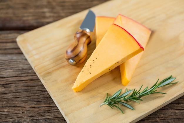 Tranches de fromage, herbes romarin et couteau sur planche de bois