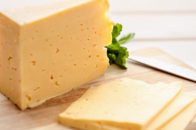 Tranches de fromage sur une planche à découper avec