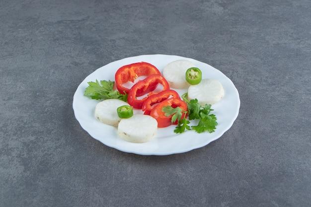 Tranches de fromage et de poivre sur plaque blanche.