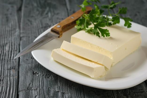 Tranches de fromage serbe avec un couteau et des feuilles de persil sur une table en bois noire.